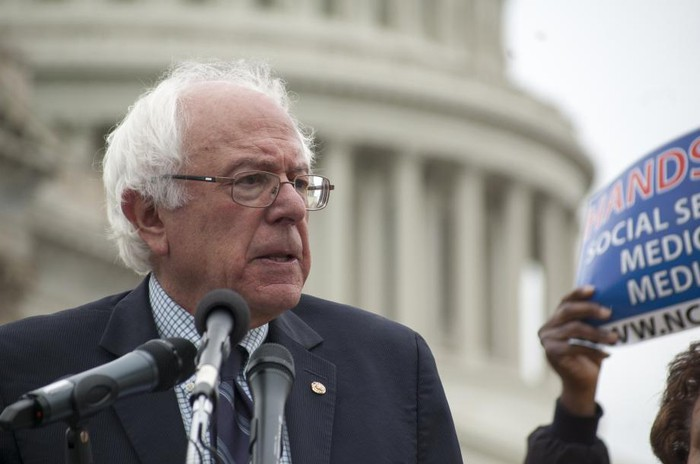 Senator Bernie Sanders giving remarks in front of the Capitol building.
