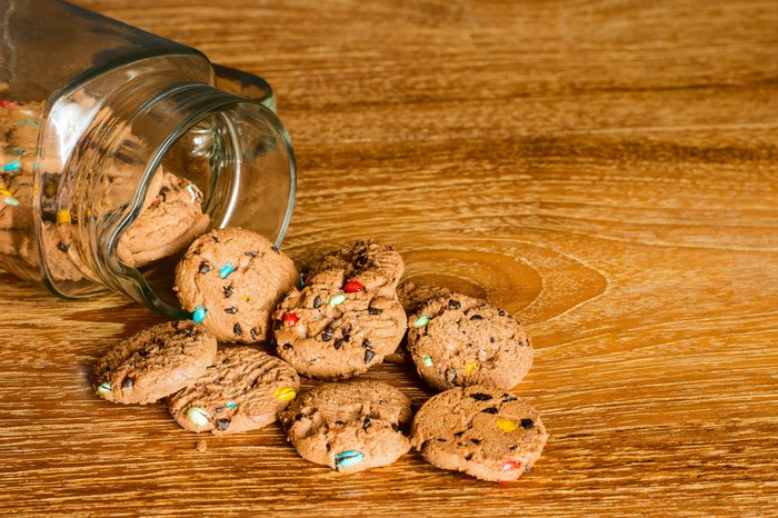 Cookies spilling out of a glass cookie jar onto a wooden table.