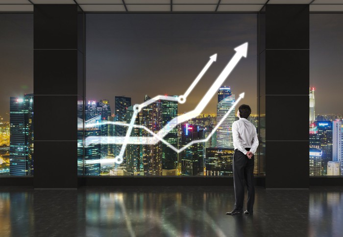 A man in business attire looks out a large window as three upward sloping lines, suggesting rising stock charts, hang superimposed over a nighttime city skyline.