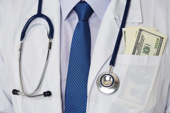 A stethoscope hangs around the neck of a man with hundred dollar bills in his pocket.