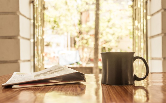 A newspaper and a mug on a table, with leafy trees seen through an open window in the background.