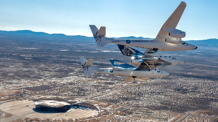 Two Virgin aircraft fly over Spaceport America in New Mexico.