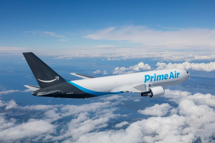 An airplane for Amazon Prime Air flies above a cloudy blue sky.
