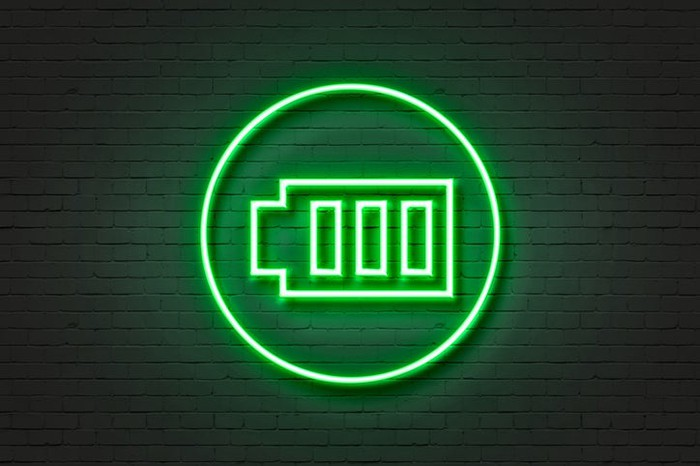 A green neon sign in the shape of a battery.