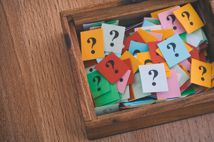 A wooden box holding paper cards with question marks on them.