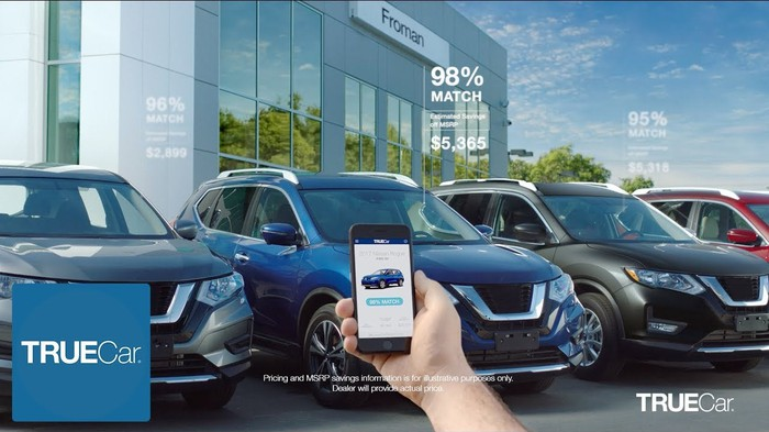 A person holding a phone running the TrueCar app, in front of a selection of new cars.