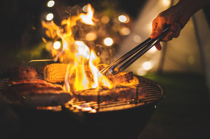Meat being barbecued at night on an outdoor grill.