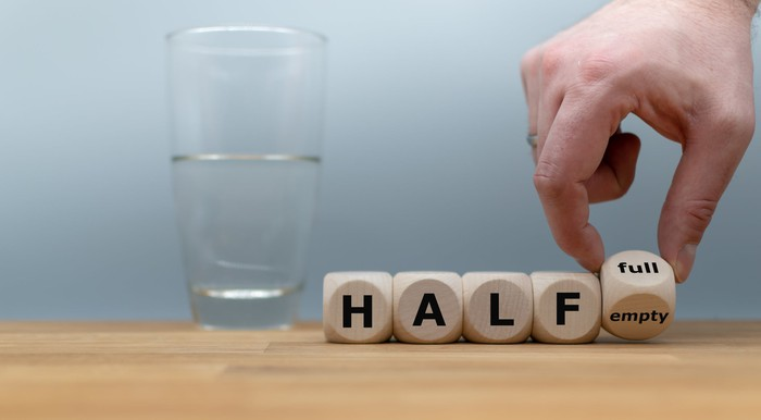 "Glass of water half full with wooden blocks spelling out ""half"" and a hand turning the last wooden block from ""empty"" to ""full"""