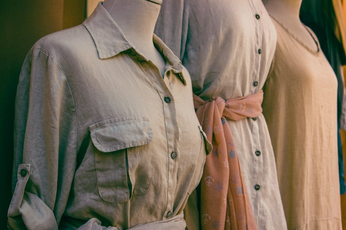 Three beige dresses are displayed on mannequins in a shop.