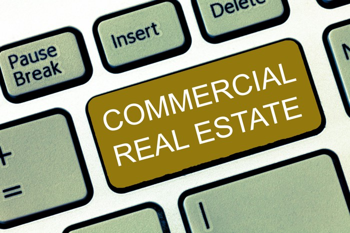 a portion of a computer keyboard is shown with a key on it saying commercial real estate