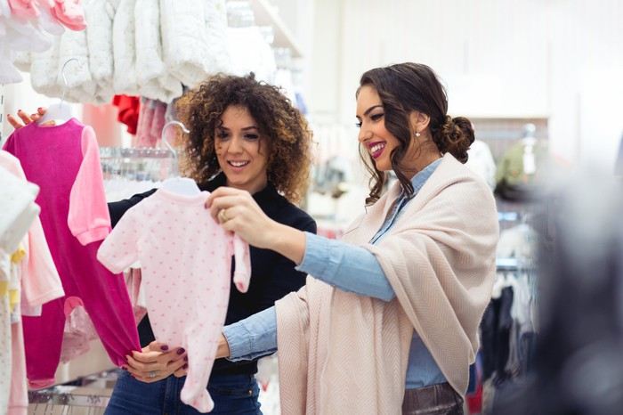 Two women shopping at a baby clothes retailer.
