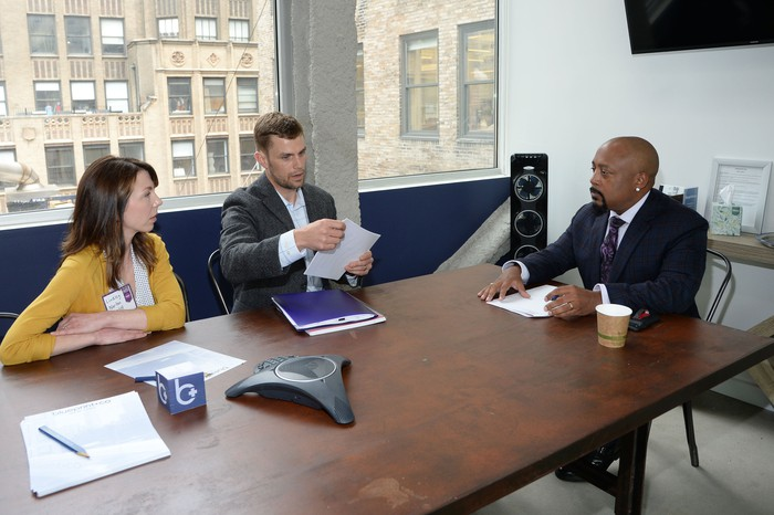 Three people sitting at a conference room table looking at papers.