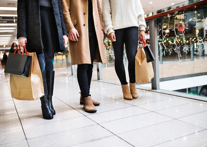 Three women holding shopping bags and standing in a mall