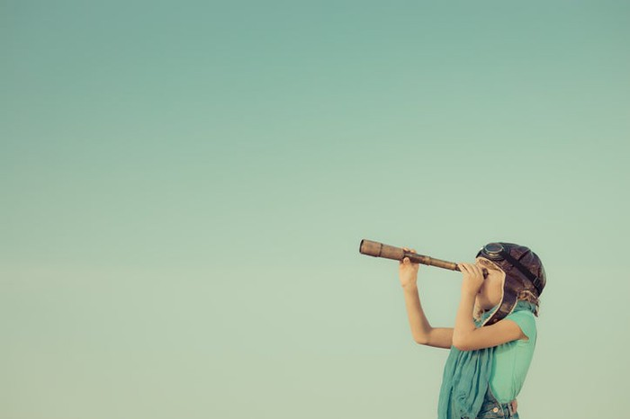 A kid looking through a telescope.