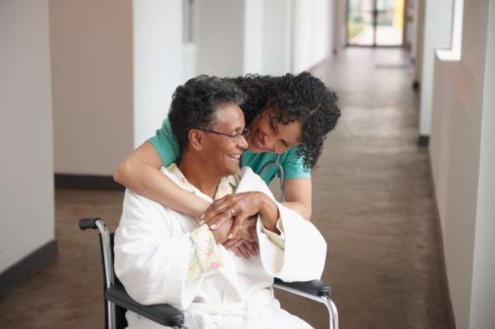 Woman patient in wheelchair being hugged from behind by female healthcare provider