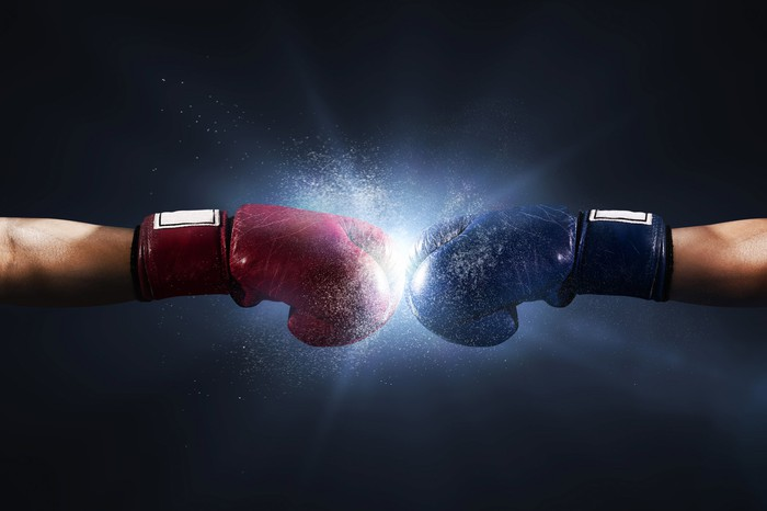 Two boxers with straight arms touch their gloves together.