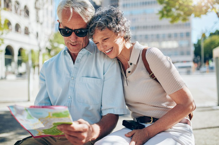 Older man in sunglasses holds a map while older woman rests her head on his shoulder and looks on