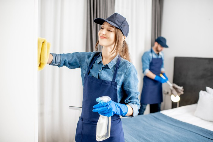 A young woman in uniform cleans a wall with a rag  and a spray bottle of cleanser in the other.