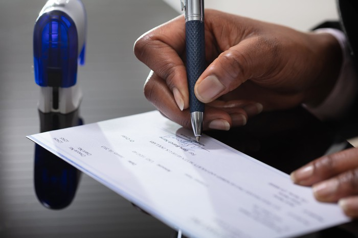 A businessperson signing a check.