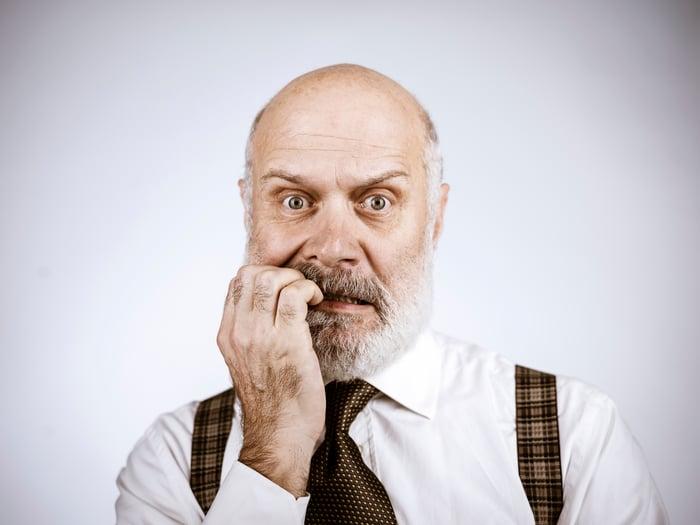 A nervous businessman chewing on his fingernails.