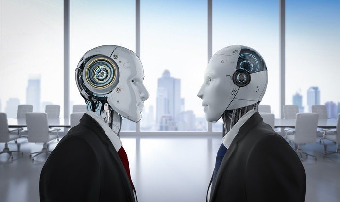 Two robots clad in suits face off in an office.