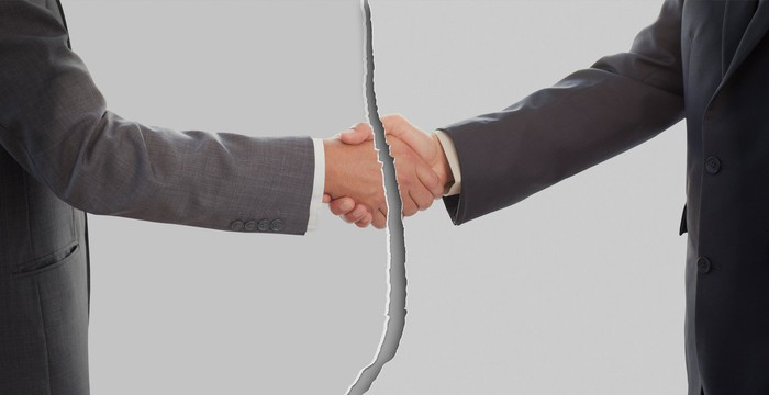 Ripped picture of two men in suits shaking hands