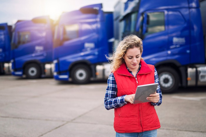 A woman using a tablet in front of a fleet of freight trucks