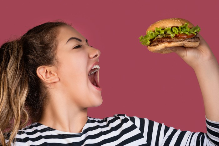 Woman taking a big bite of a burger