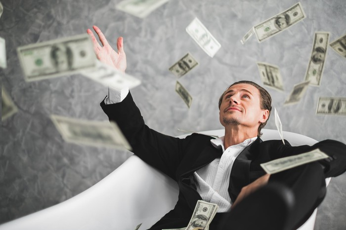A man in a suit sitting in a chair with money raining down around him.