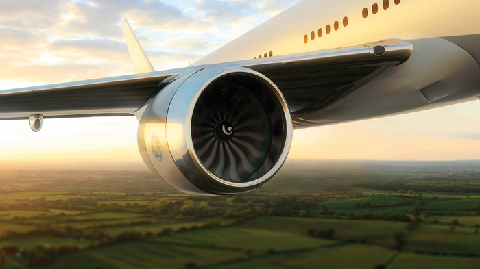 A GE9X Engine hangs off the wing of a plane in flight.