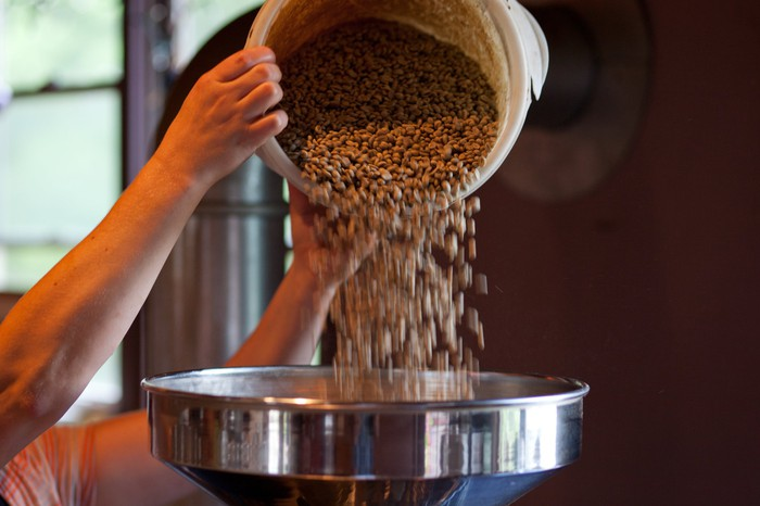 Close-up of coffee beans being poured into a commercial roaster.