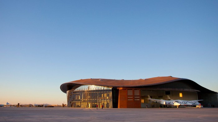 Spaceport America, Virgin Galactic's headquarters in New Mexico, a hangar with glass windows in front with a Virgin Galactic spaceship pictured in front of it.
