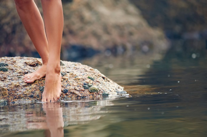A swimmer dipping their toe in a lake.
