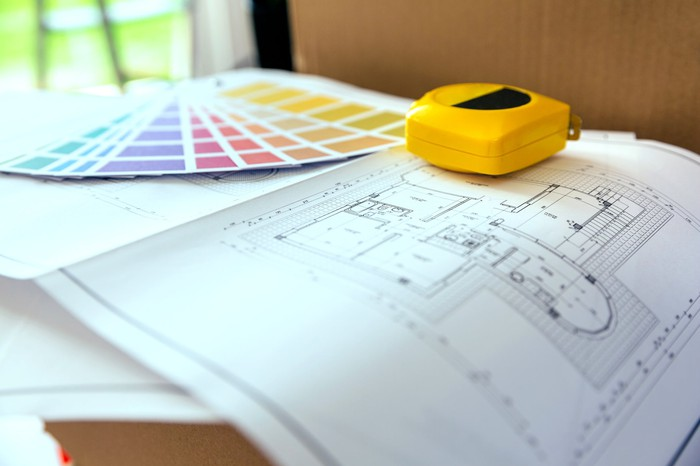 Architectural plans, color samples, and a tape measure on a table
