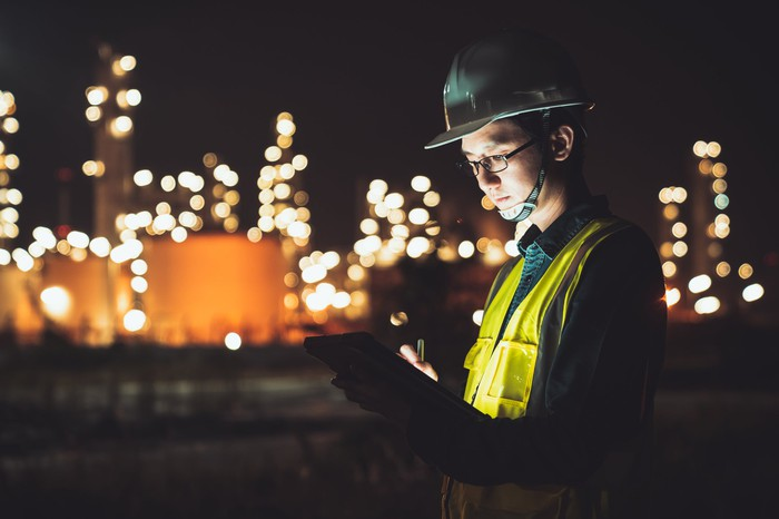 An engineer working at night at a refinery