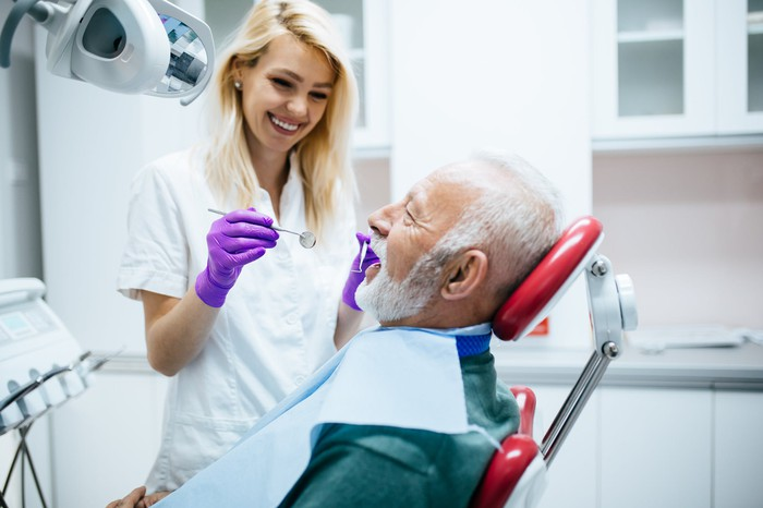 Smiling woman in white scrubs holding mirror next to older man in dentist's chair
