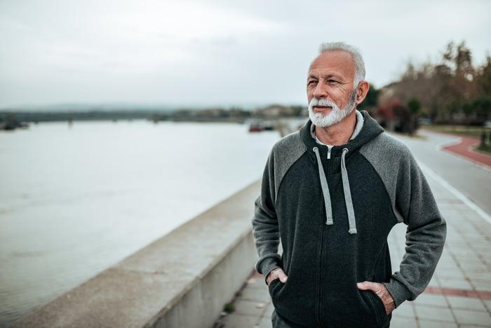 Older man outdoors putting hands in sweatshirt pockets