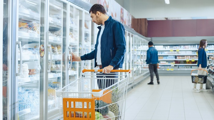 Man shopping in a frozen-food aisle