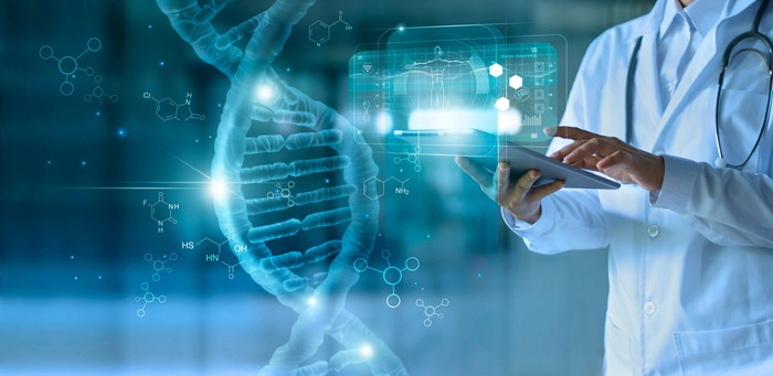 Abstract picture of a scientist touching a tablet with a DNA strand and other information appearing.