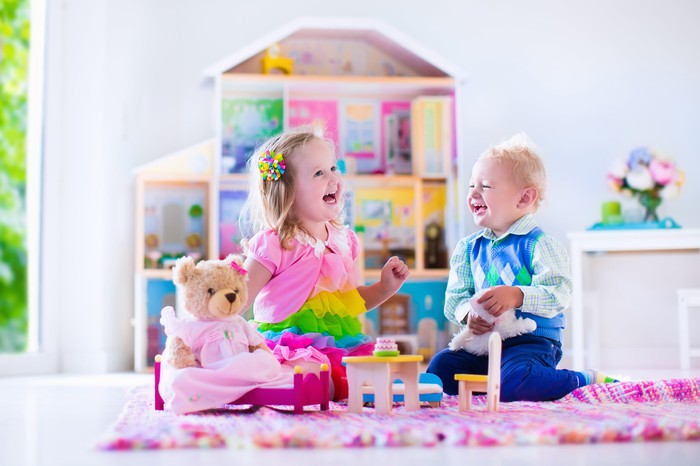 A little girl and boy play teatime with a stuffed bear in front of a doll house.