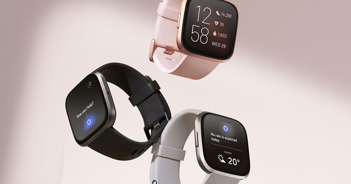 Three Fitbit Versa smartwatches, one each displayed in black, pink, and silver.