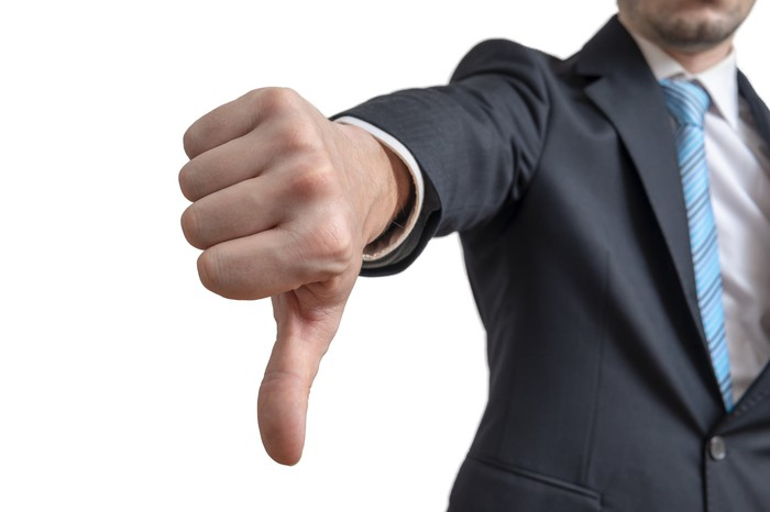Man in business suit with a big thumb pointing down