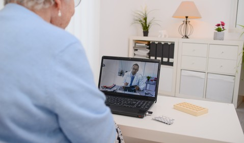 An elderly woman videoconferencing with a doctor on a laptop telemedicine