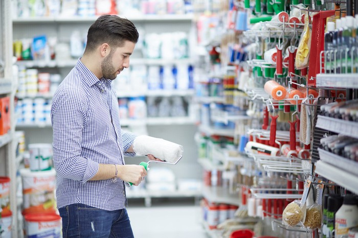 A man standing in the aisle of a home-improvement store holding a paint roller