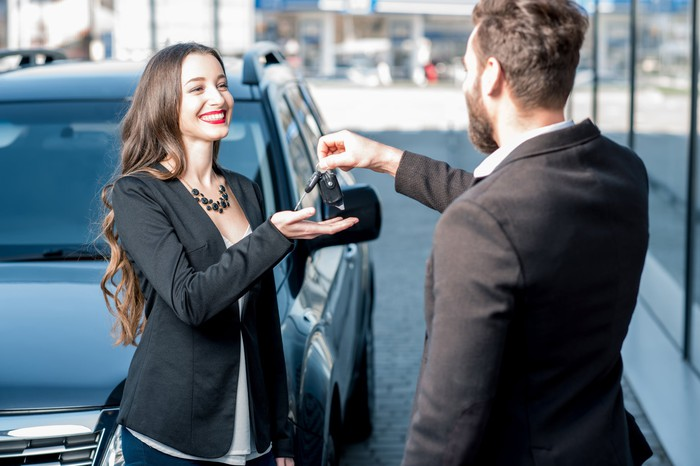 A young woman receives keys for a new car from a car salesman.