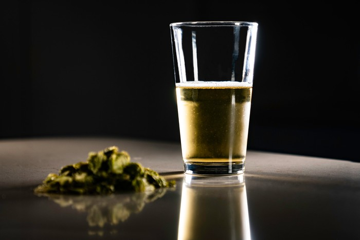 Cannabis buds next to a glass of beer