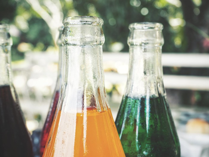 Close-up of glass soda bottles in various flavors.