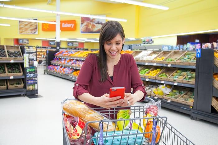 Walmart customer smiling and looking at smartphone while pushing cart.
