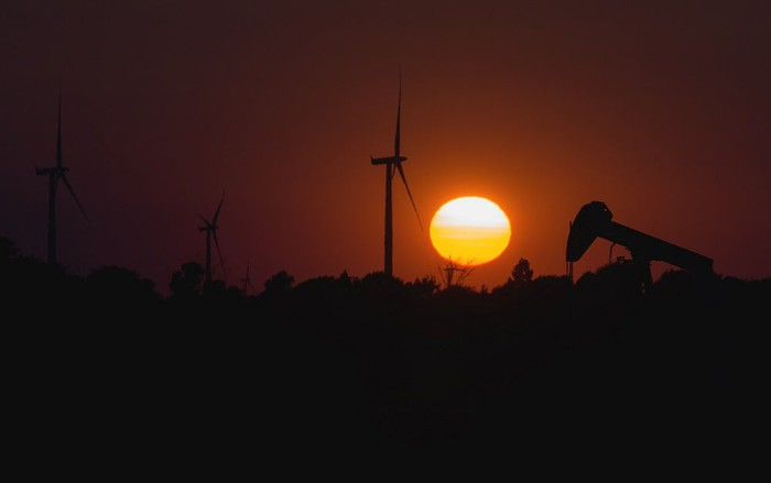 Wind turbines and oil pumpjacks with sun in background.