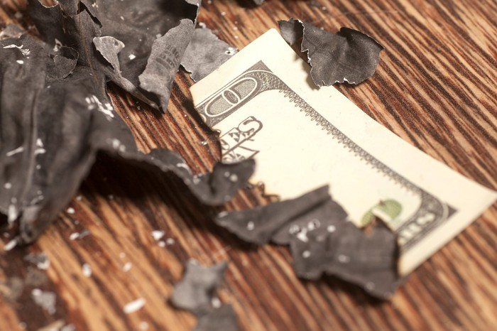 A burned piece of cash lies on a table.